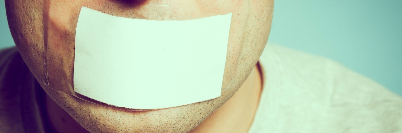 A man with a piece of paper taped over his mouth