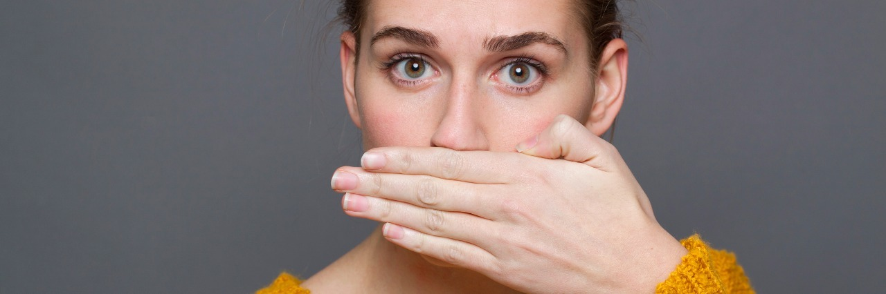woman in a yellow sweater covering her mouth with her hand