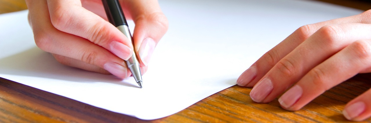close up of a womans hands writing on a sheet of paper at a desk