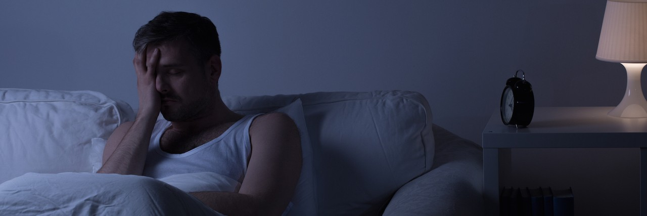 man up at night sitting in bed