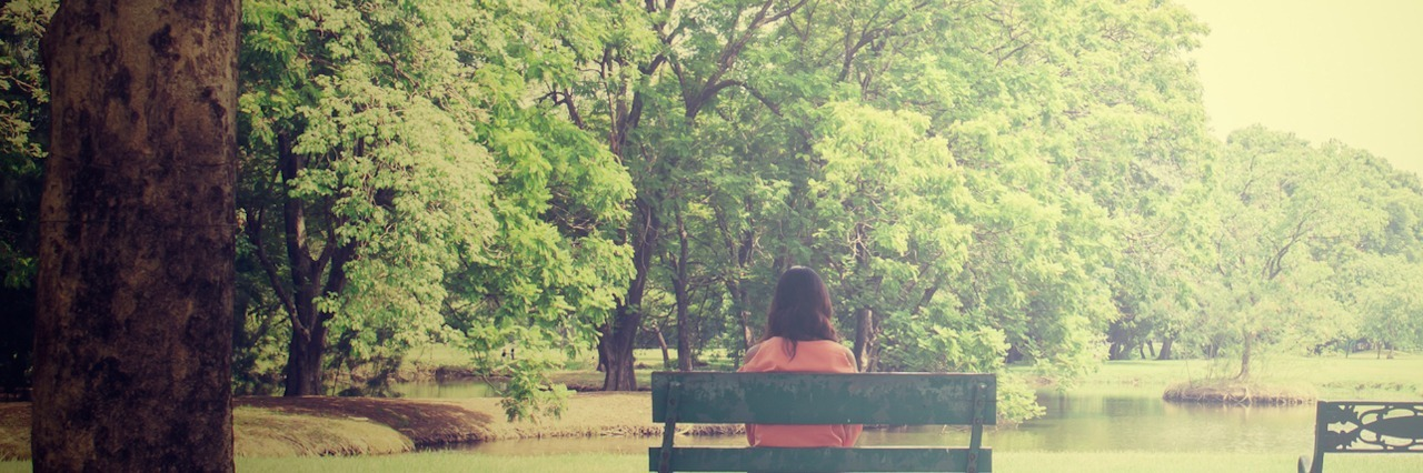 Woman sitting on bench in a park