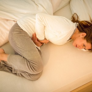 young woman lying on bed and holding hands on her stomach.