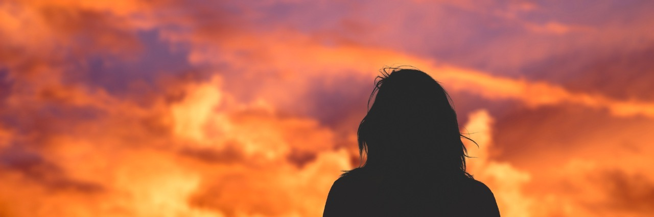 silhouette of a girl watching the sunset