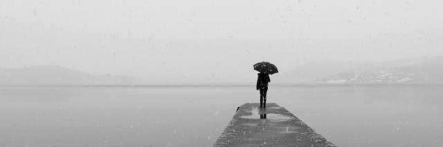 lonely woman with an umbrella standing alone on a dock under a grey sky