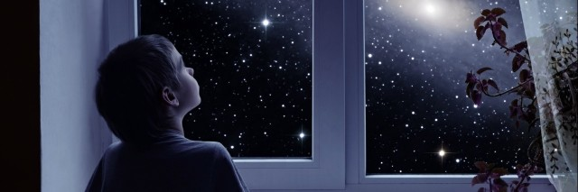 little boy looking out a window at the night sky
