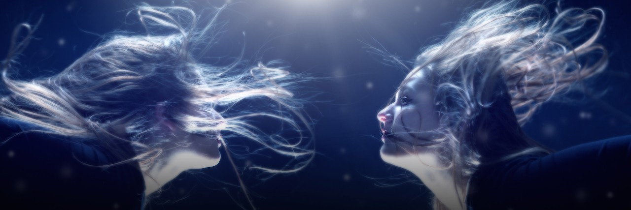 two woman under water facing each other