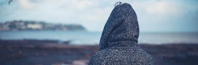 Woman in hooded coat walking on beach