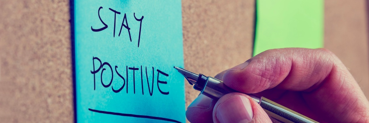 Retro image of a male hand writing Stay positive on blue post it paper pinned on cork bulletin board.