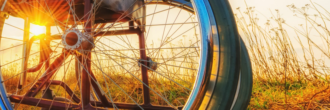 Wheelchair on the meadow at sunset.