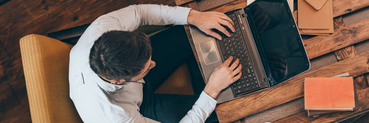 Top view of young man working on laptop while sitting at his working place