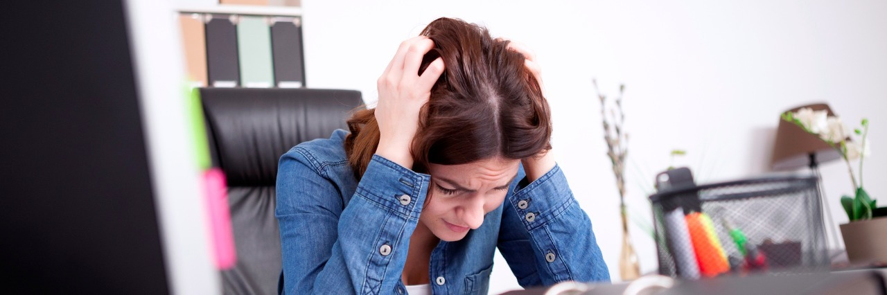 woman having a meltdown at her desk in the office