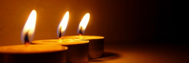 three tea light candles burning in a row