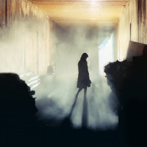 silhouette of a woman walking in a misty underground tunnel