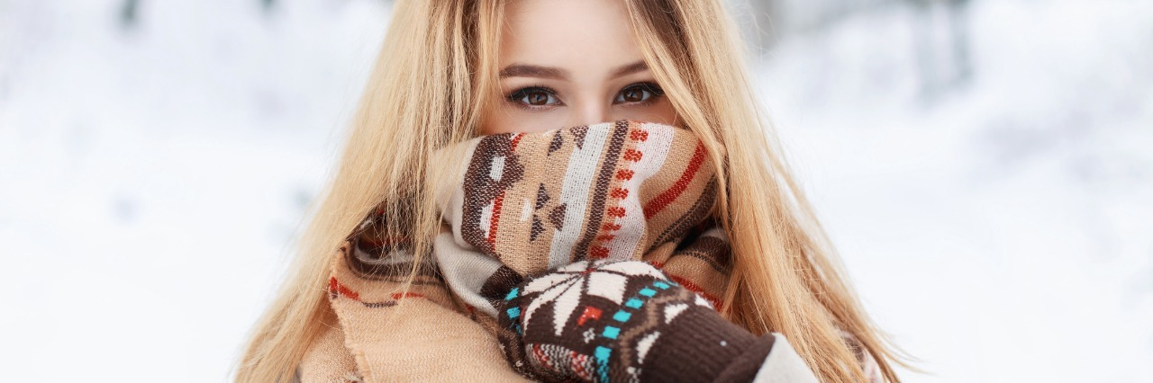 blonde woman standing outside in the snow wearing a heavy coat, scarf, and gloves