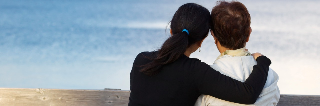 Closeup of mother with mature daughter holding her while sitting on wooden bench looking outward at the lake