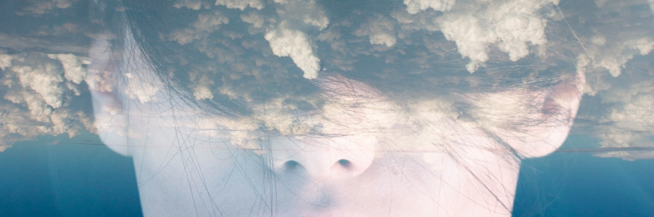 Double exposure portrait of woman with clouds on her head