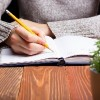 Woman writing in notebook with pencil