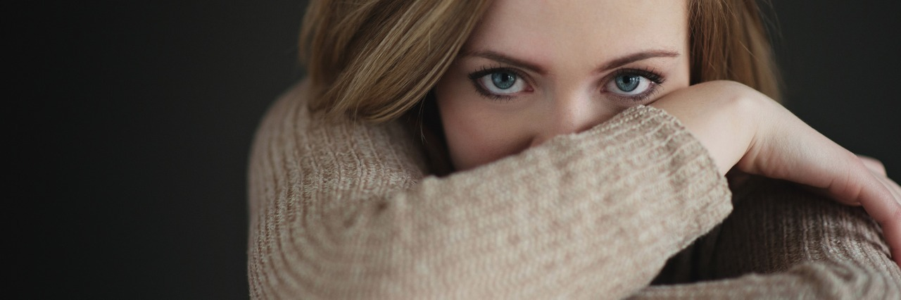 woman in light brown sweater crossing her arms and covering part of her face
