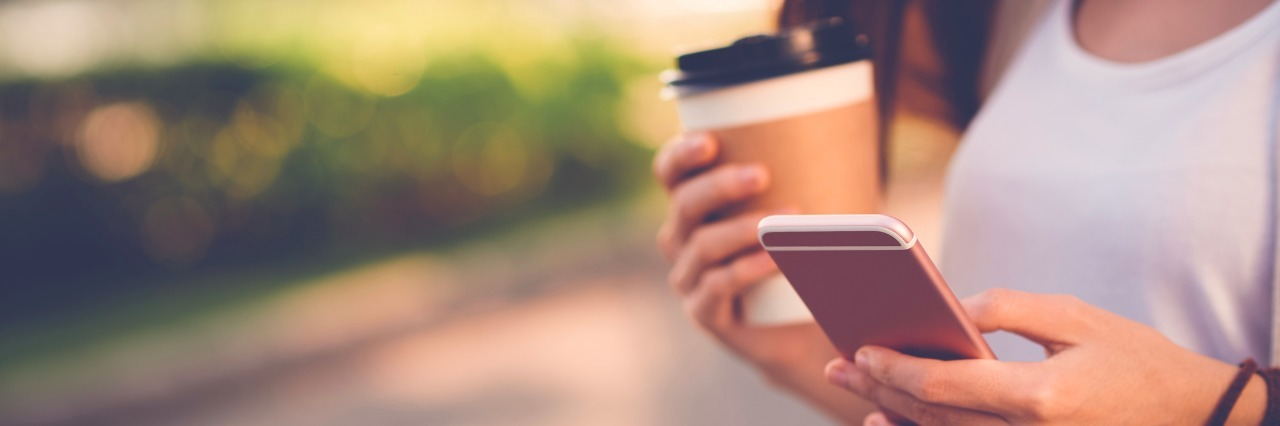 Close-up image of woman texting and drinking coffee outdoors