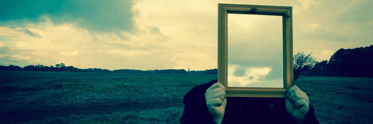 A man holding up a mirror over his face ,which reflects the sky