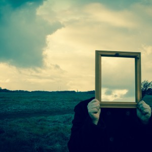 Man with mirror in front of face, reflecting sky