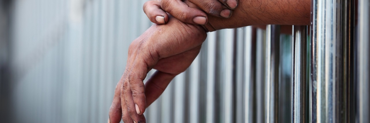 hands coming out of a prison cell