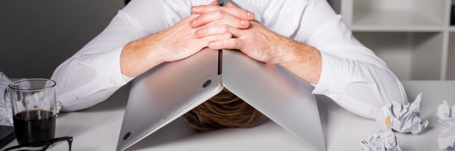 a man seated at his desk hiding his head under a laptop