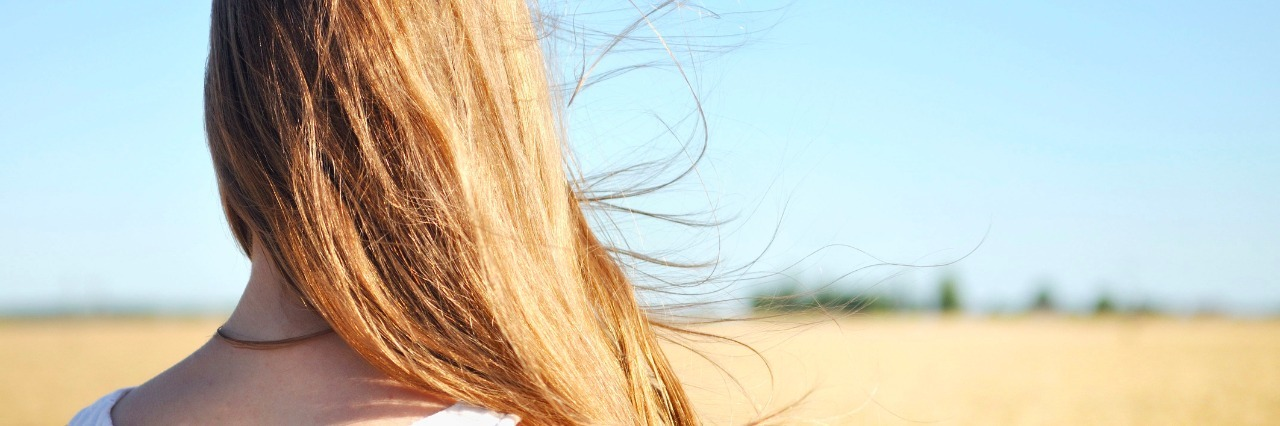Wind flutters young girls hair who is standing in the field