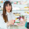 pharmacist handing a customer a prescription