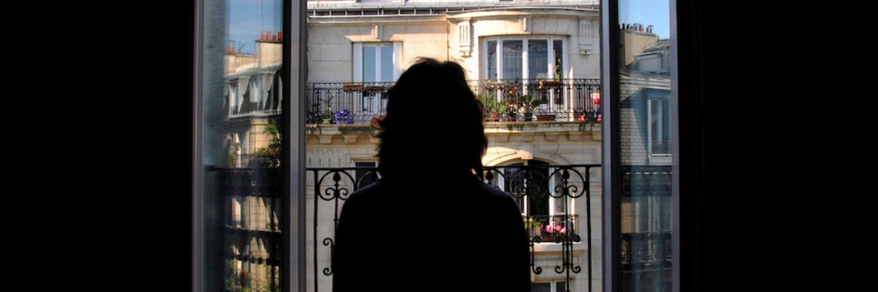 A woman in a dark room looking out a window