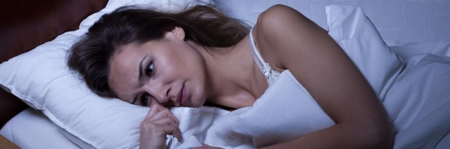 woman laying in bed with eyes open