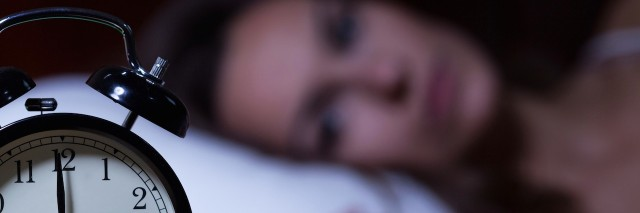 woman in bed looking at her alarm clock