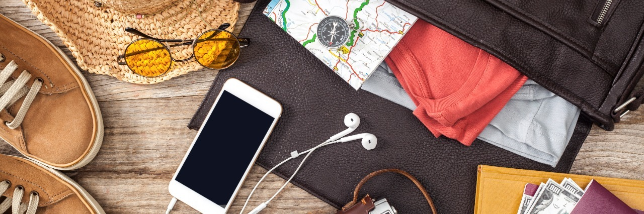 suitcase filled with maps on a table with an iphone, headphones, camera, hat, sunglasses, shoes, and money