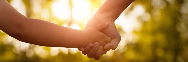 Mother and child holding hands at sunset in park