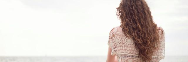 woman sitting facing ocean