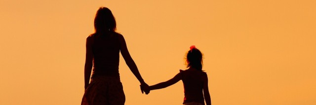 Silhouette of a woman holding hands with her daughter