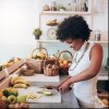 Shot of young african woman working at juice bar and cutting fruits. Female bartender making fresh juice.