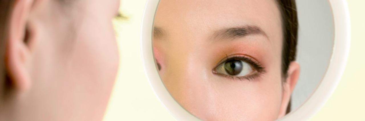 a close up of a woman looking at herself in a small handheld mirror