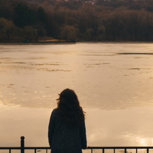 Woman facing lake at sunset in the winter