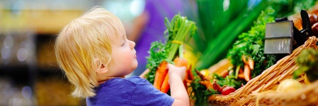 young boy in supermarket grabbing carrots off a produce shelf