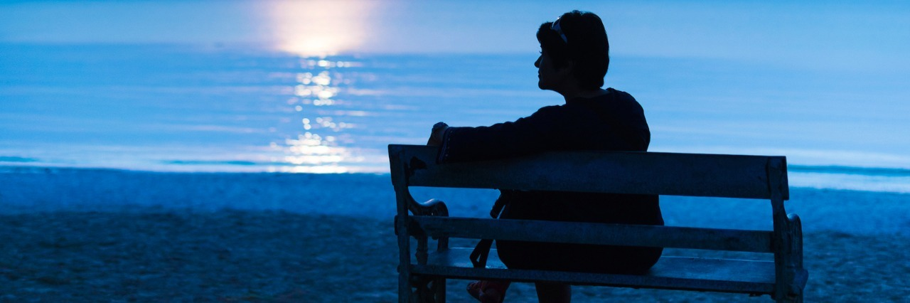 Woman sitting on bench at the beach at night
