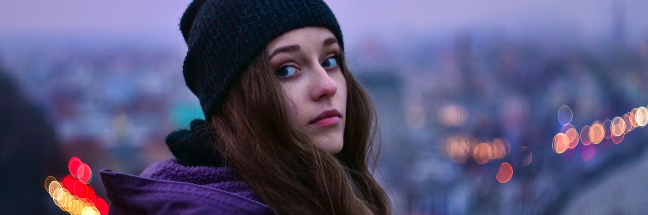 A girl in a beanie looking out at a city