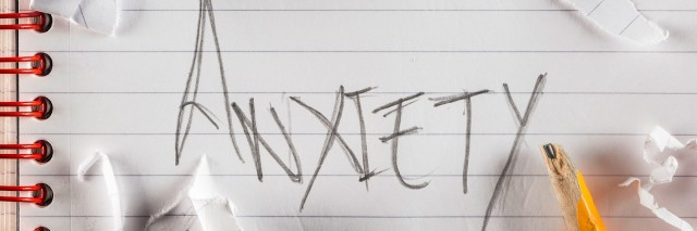 The word anxiety written in pencil surrounded by crumbled up pieces of paper