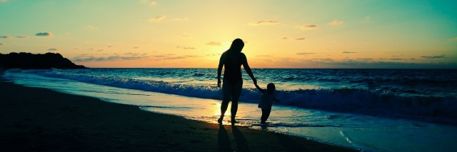 mother and young daughter holding hands at the beach
