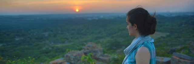 Girl Looking at Sunset Over Ruins and Field India