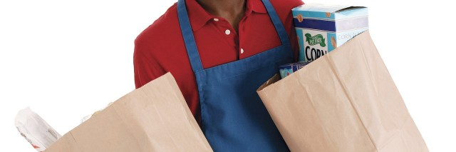 Employee holding grocery bags.