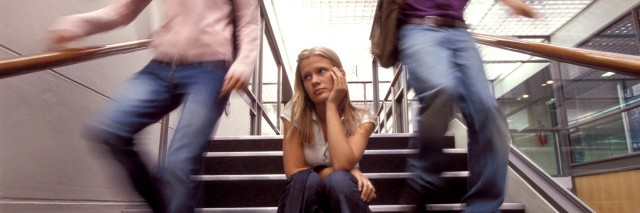 sad female student sitting on stairs while others move around her