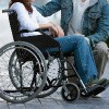 Man with woman in wheelchair.