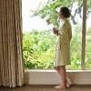 older woman wearing a bathrobe and holding a mug looking out her window at greenery