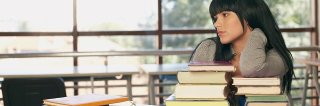 female high school student leaning on a table and gazing out a window next to a large stack of books